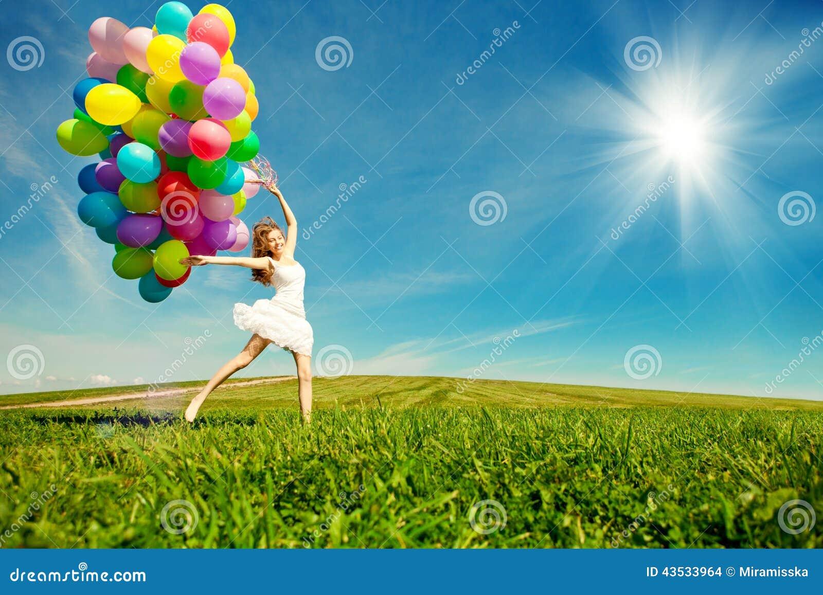 Mujer del feliz cumpleaños contra el cielo con vagos arco iris-coloreados del aire
