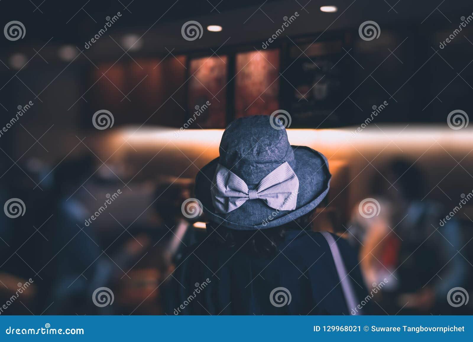 Mujer del foco selectivo que espera en línea para pedir el café en la tienda del café