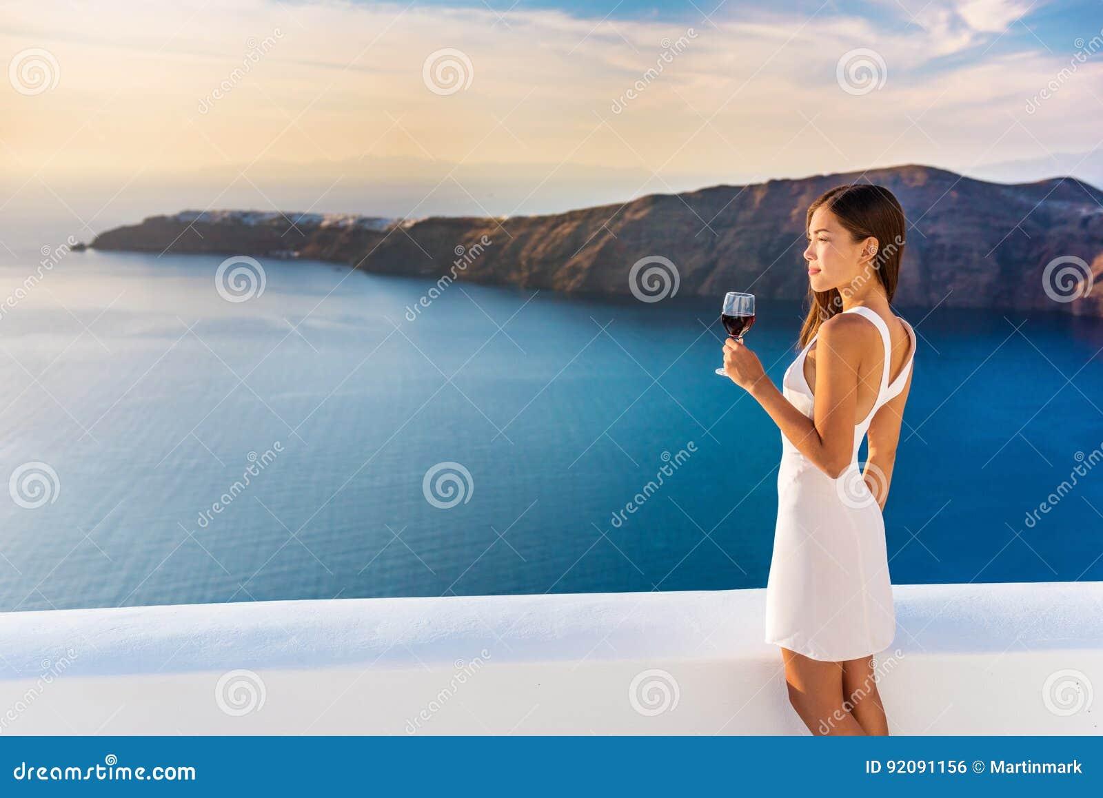 Mujer del hotel de lujo que bebe el vino rojo en Santorini