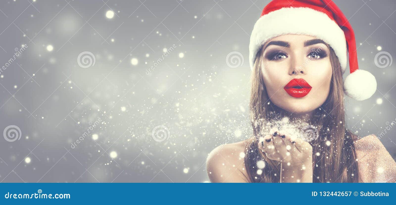 Mujer del modelo de la belleza en la nieve que sopla del sombrero de Papá Noel en su mano Muchacha de la moda del invierno de la