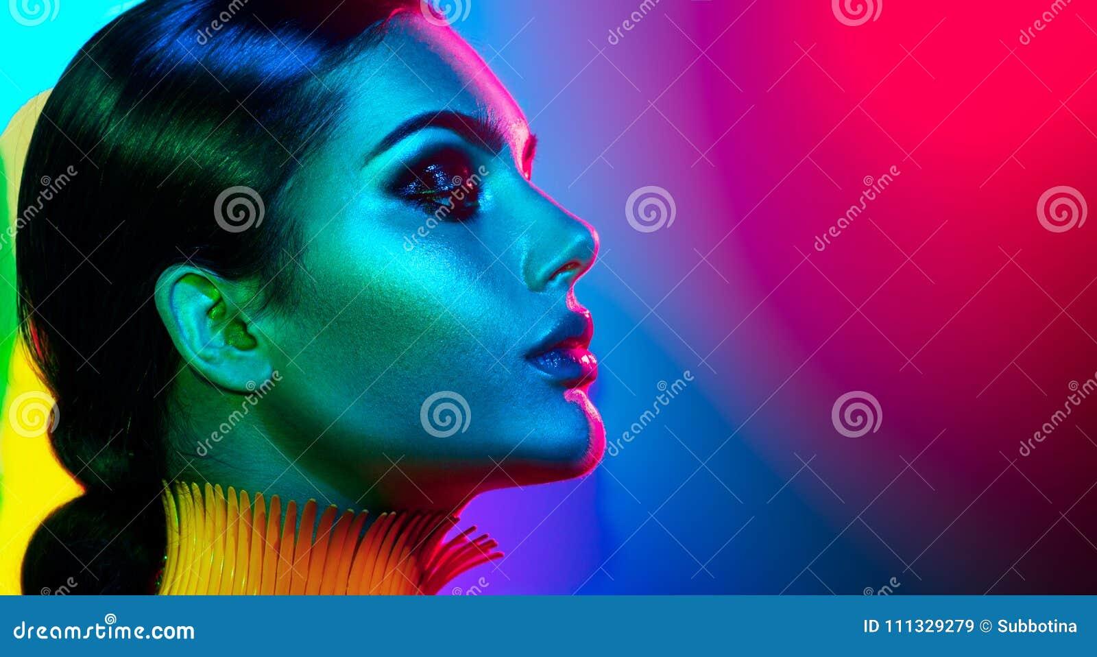 Mujer del modelo de moda en la presentación brillante colorida de las luces Retrato de la muchacha atractiva con maquillaje de mo