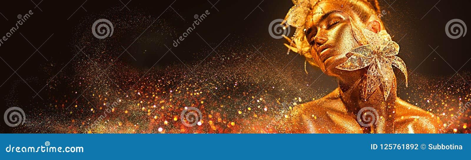 Mujer del modelo de moda en las chispas de oro brillantes coloridas que presentan con la flor de la fantasía