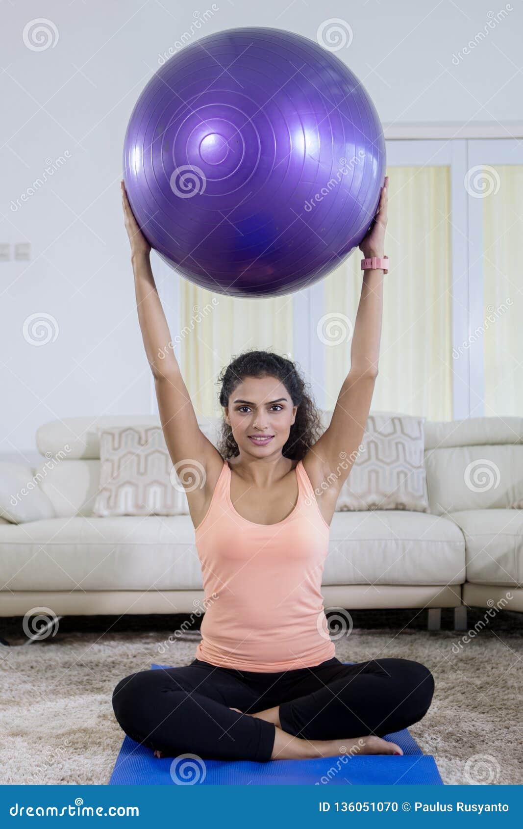Imagen de la mujer del pelo rizado que levanta una bola de la yoga mientras  que ejercita en la sala de estar tirado en casa 324ba5bad79d