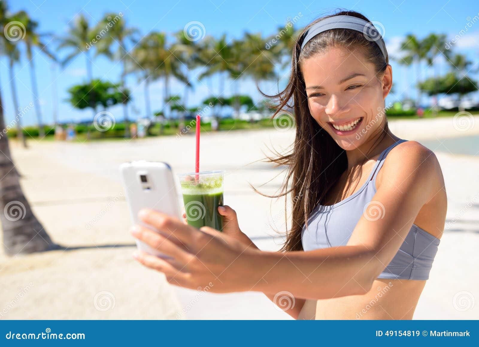 Mujer del selfie de la aptitud que bebe el smoothie verde