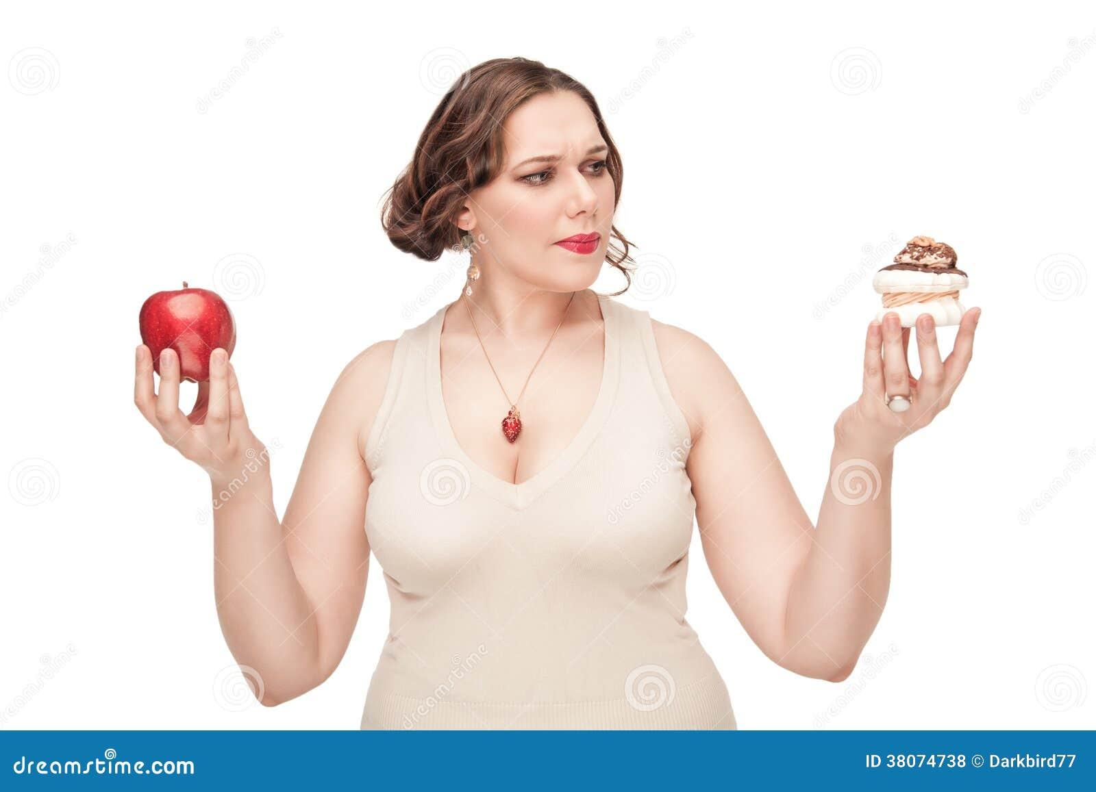 Mujer del tamaño extra grande que toma la decisión entre la manzana y los pasteles