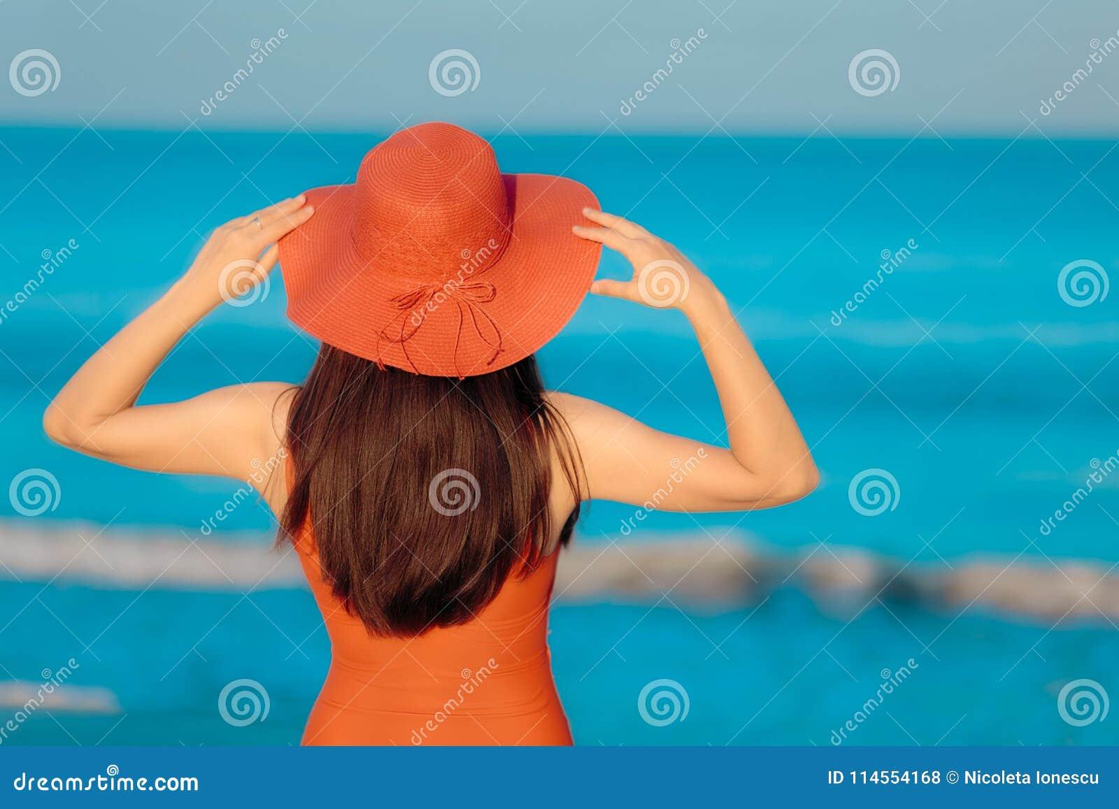 Mujer del verano con Sunhat que mira el mar
