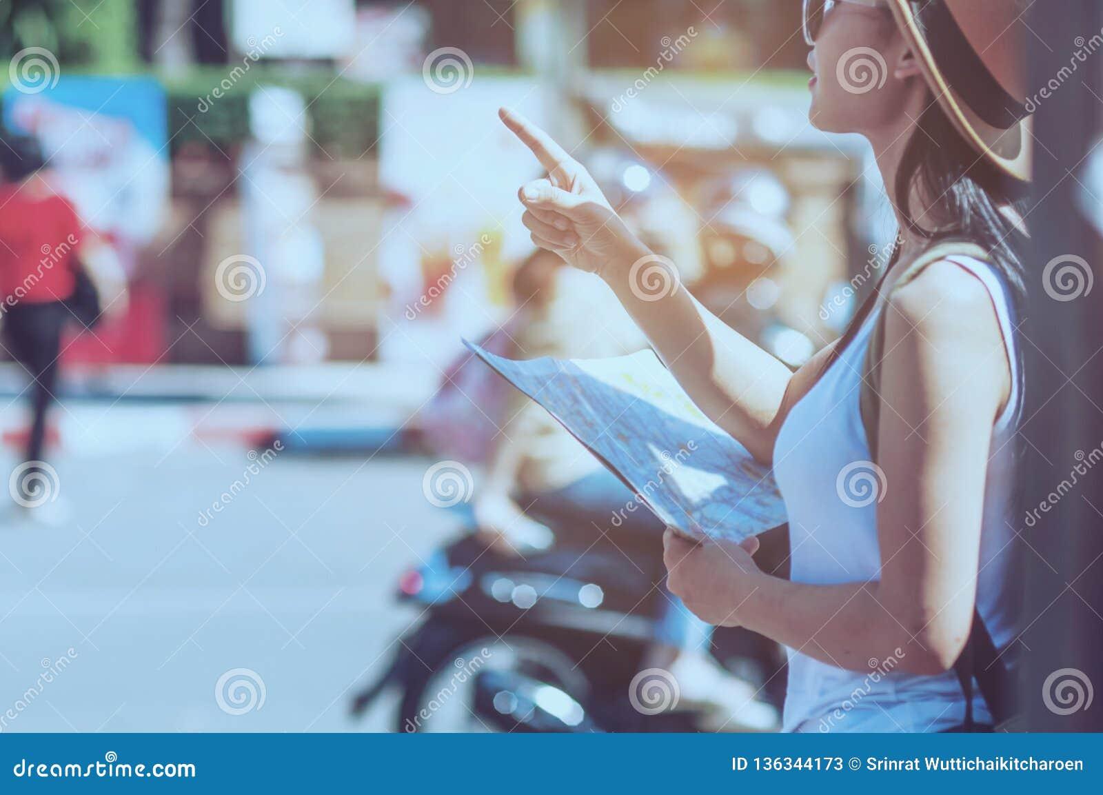 Mujer del viaje turístico que mira el mapa mientras que camina
