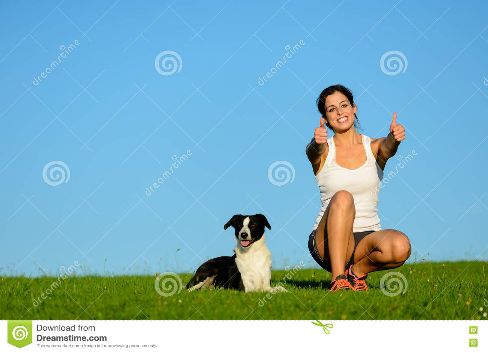 Mujer deportiva acertada que toma un resto de ejercicio con su perro