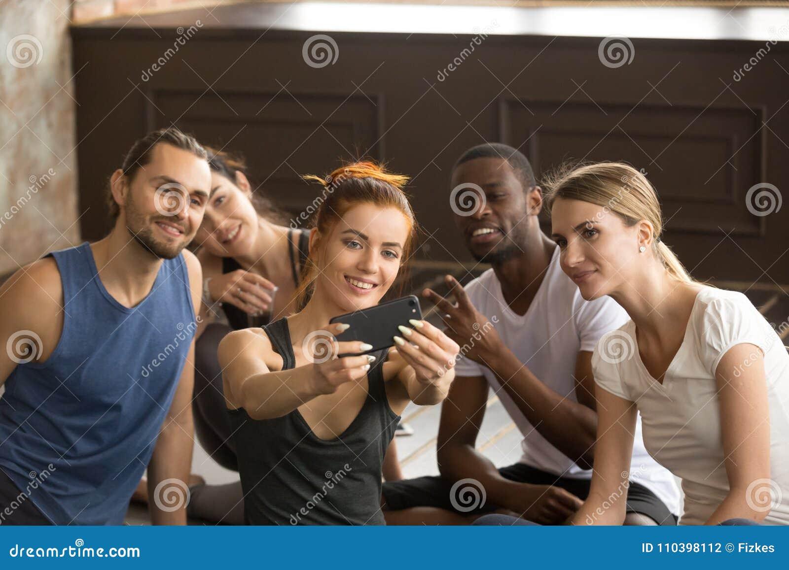 Mujer deportiva atractiva que sostiene el teléfono que toma el selfie del grupo en el tra