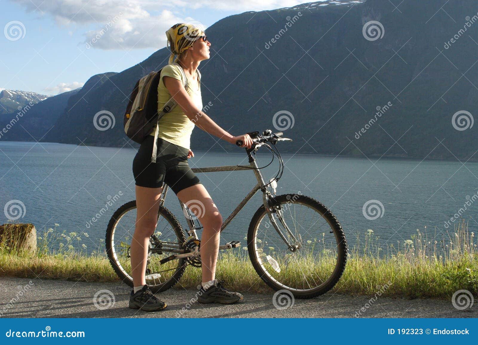 Mujer deportiva con la bici en las montañas