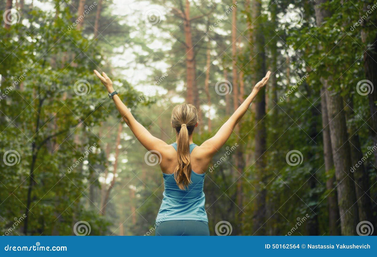 Mujer deportiva de la aptitud sana de la forma de vida temprano en área del bosque