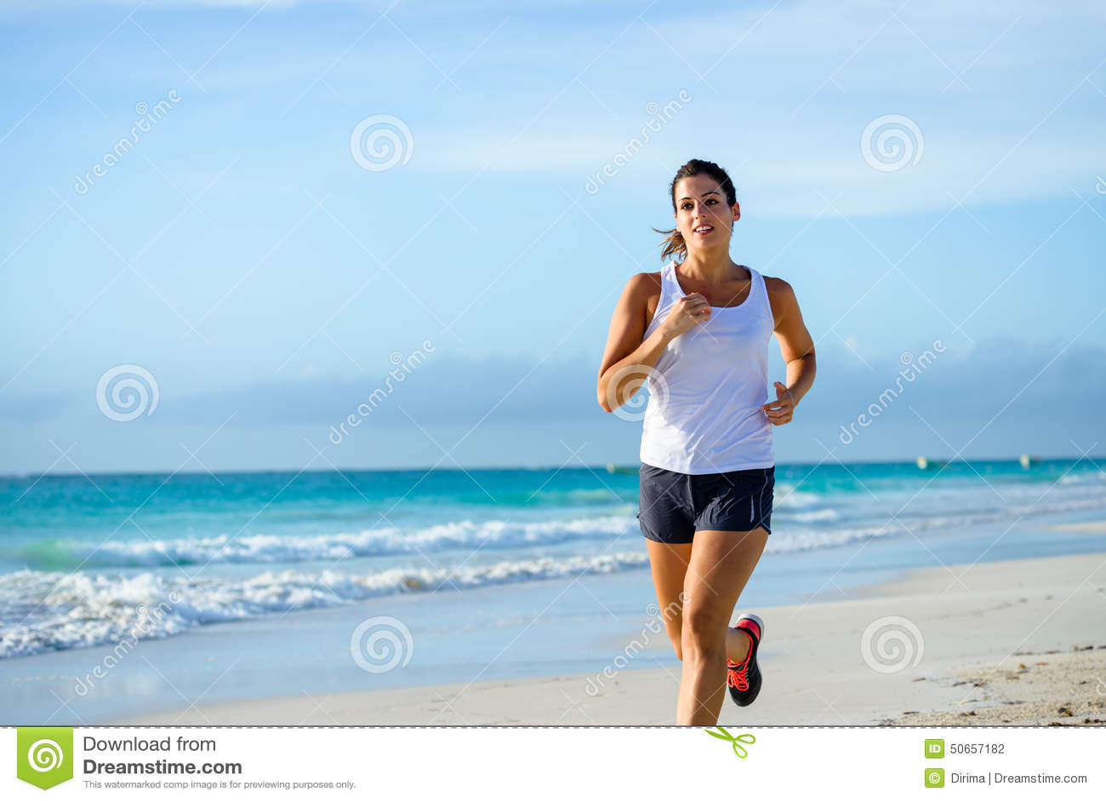 Mujer deportiva que corre en la playa tropical