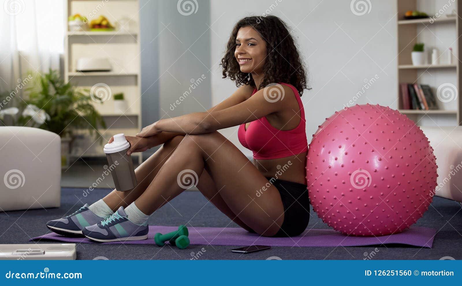 Mujer deportiva que se sienta en piso en el equipo del gimnasio, sosteniendo la botella, cóctel del suplemento
