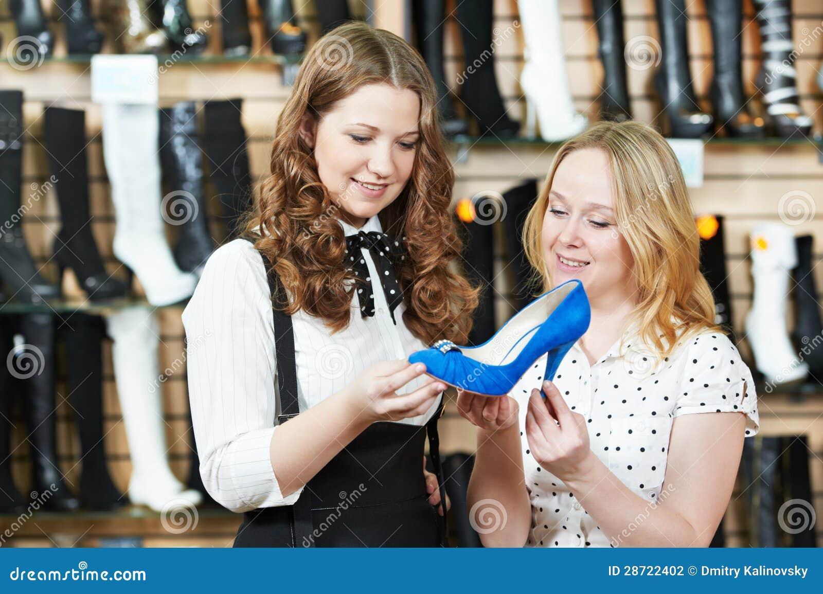 Dos mujeres jovenes que eligen los zapatos durante compras del calzado