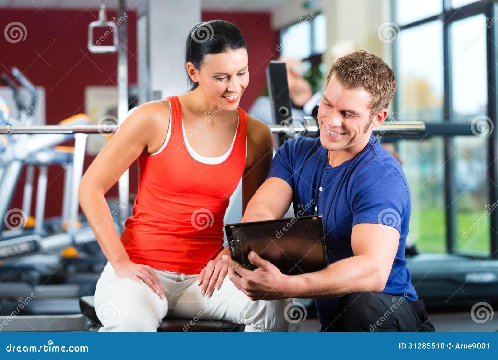 Mujer e instructor personal en gimnasio de la aptitud
