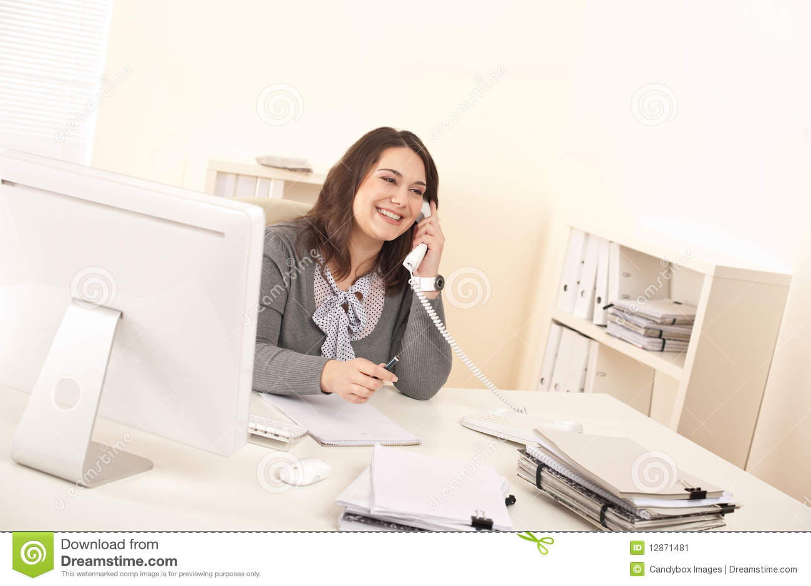 Mujer ejecutiva joven que habla en el tel fono en la for Telefono de la oficina