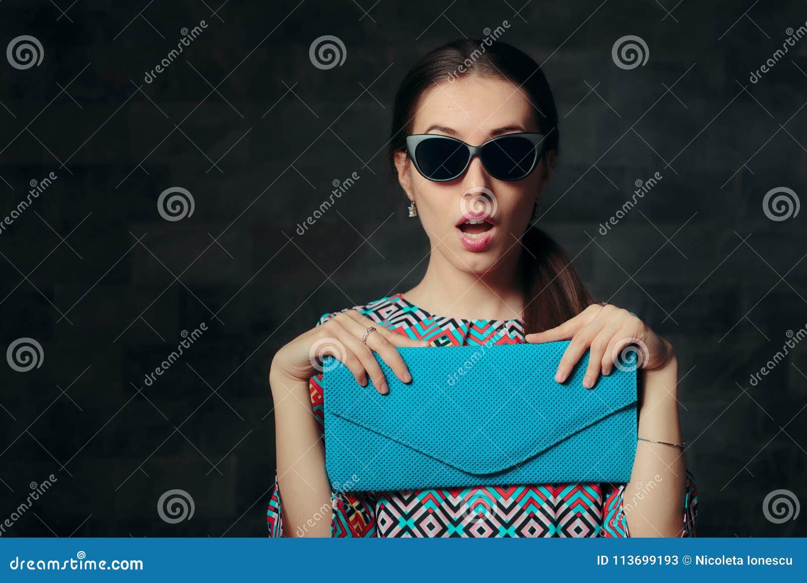 Mujer elegante con el monedero retro de Cat Eye Sunglasses y del embrague