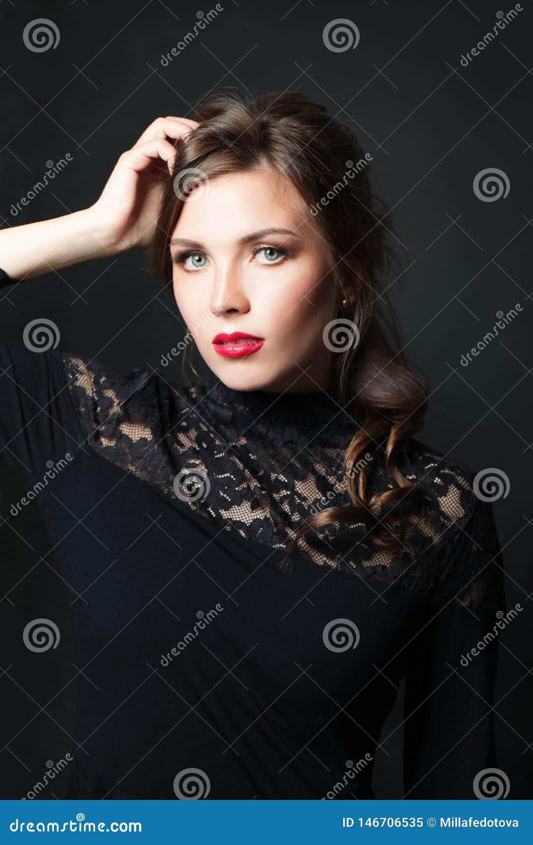 Mujer elegante con el pelo rojo del maquillaje de los labios en fondo oscuro