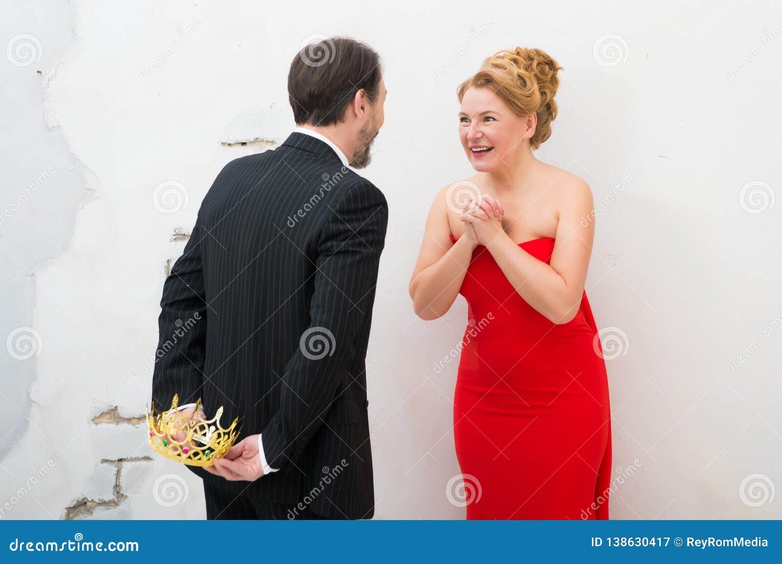 Mujer elegante contenta que guarda las manos juntas mientras que cuenta con un presente