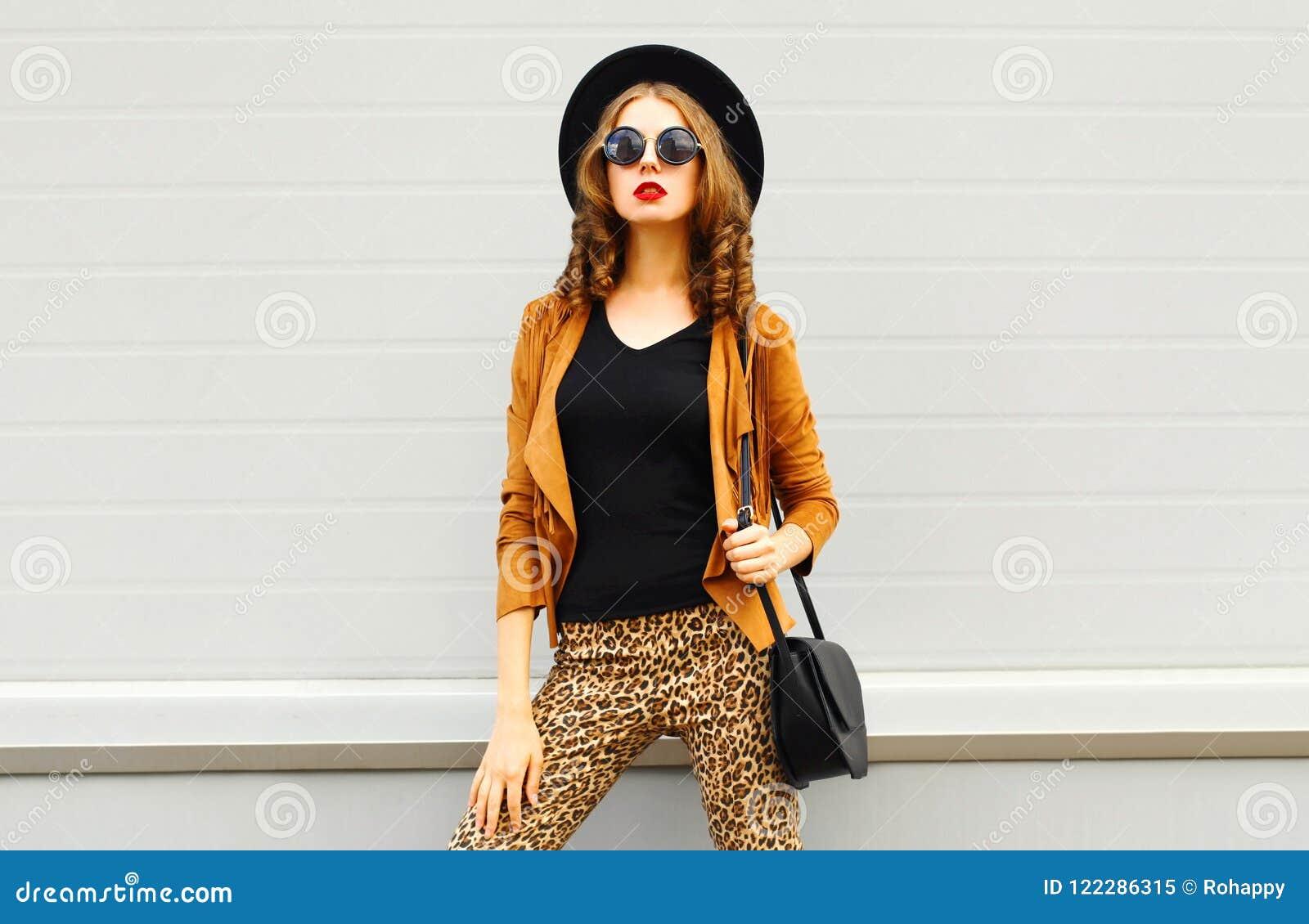 Mujer elegante hermosa que lleva un sombrero elegante retro, gafas de sol, una chaqueta marrón y un bolso negro