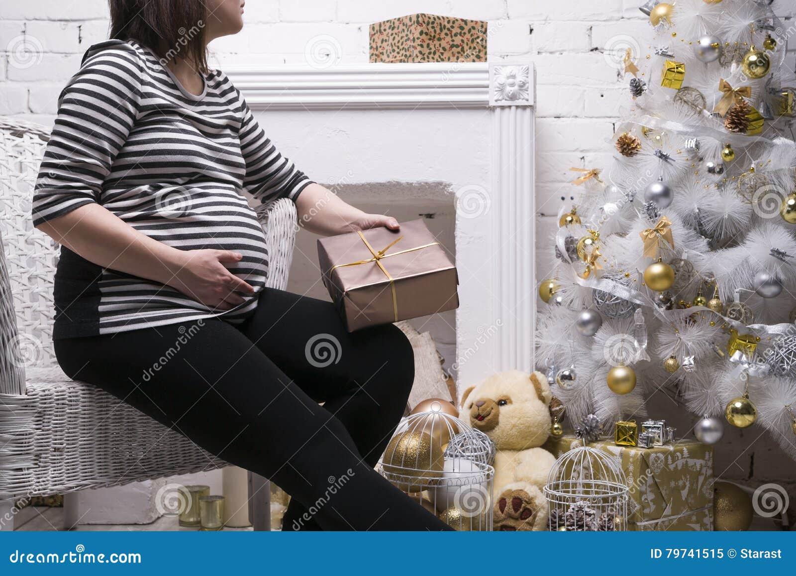 Mujer embarazada de los jóvenes con la caja de regalo que presenta en el fondo del árbol de navidad