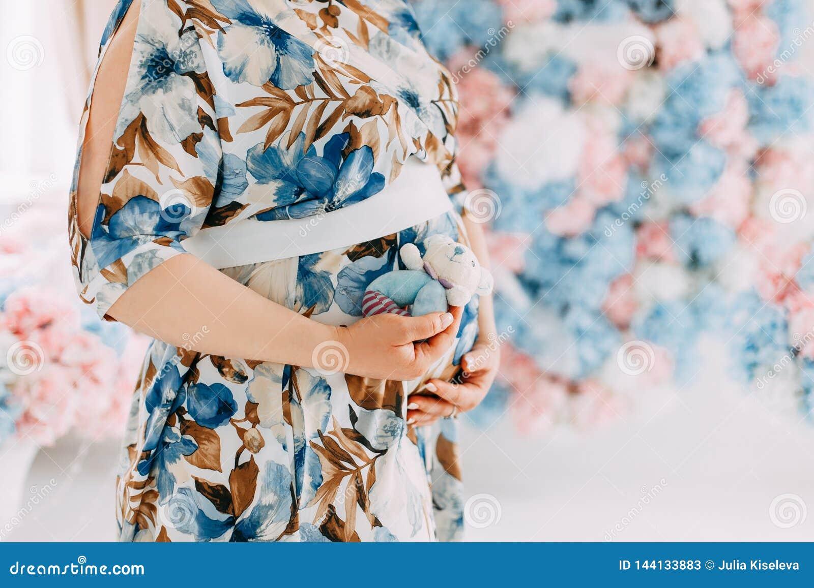 Mujer embarazada en el vestido azul delicado que frota ligeramente su vientre