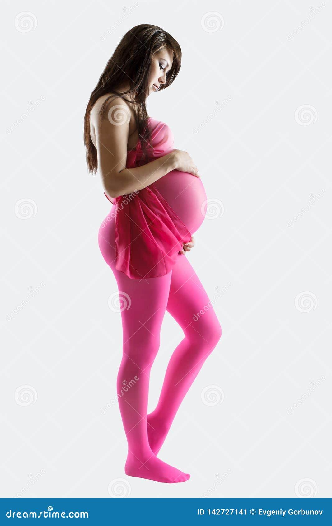 Mujer embarazada en la oferta rosada de los leggens que se sostiene el vientre, aislado