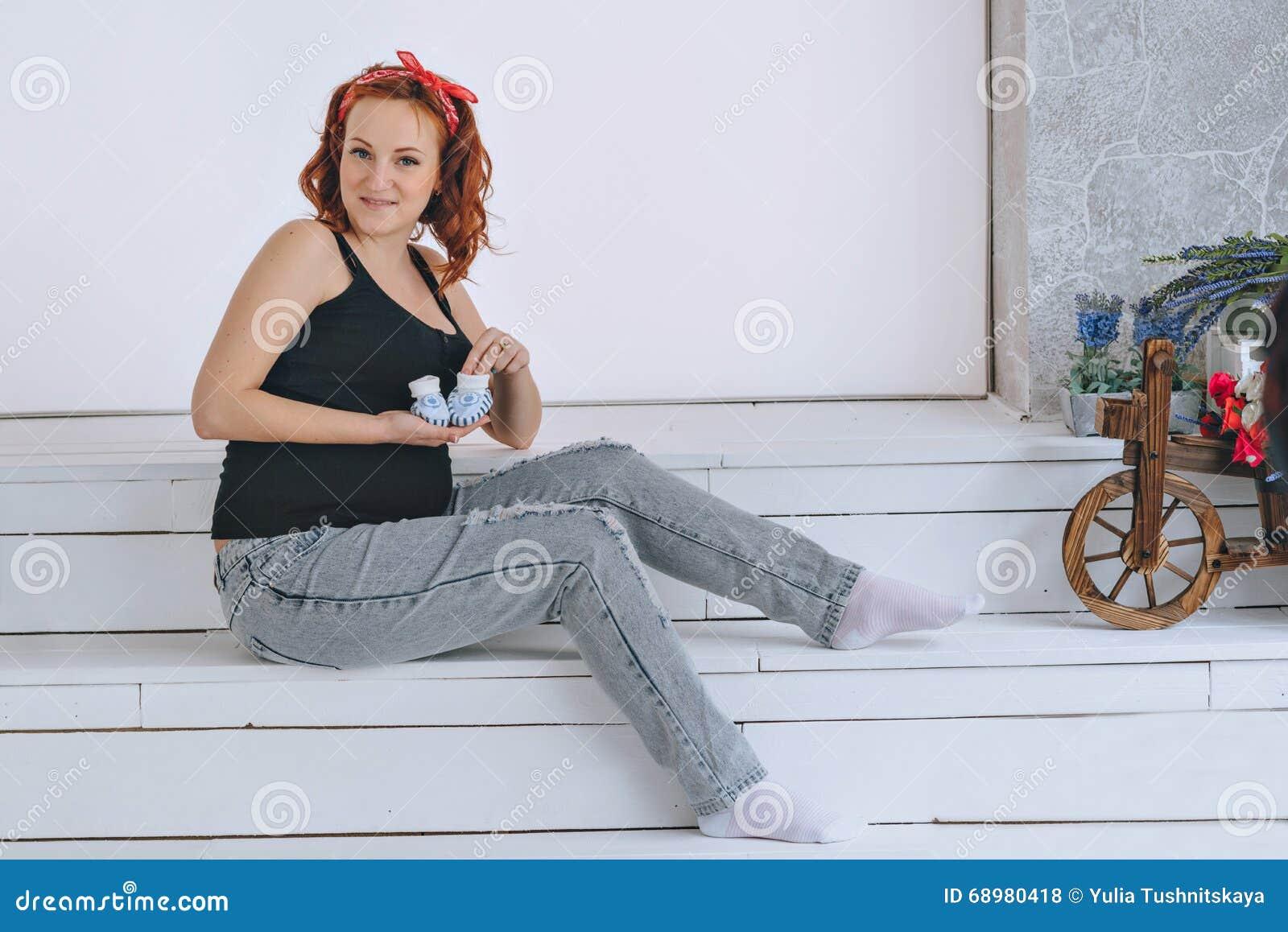 Mujer embarazada feliz que lleva a cabo botines, con un vendaje rojo en su cabeza En un fondo ligero Jóvenes pelirrojos del embar