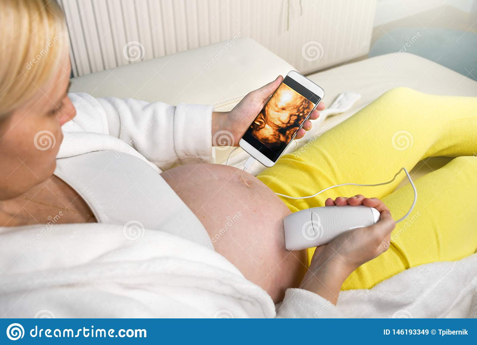 Mujer embarazada moderna que se sienta en un sof? blanco en casa que relaja y que hace sola el ultrasonido digital 3D