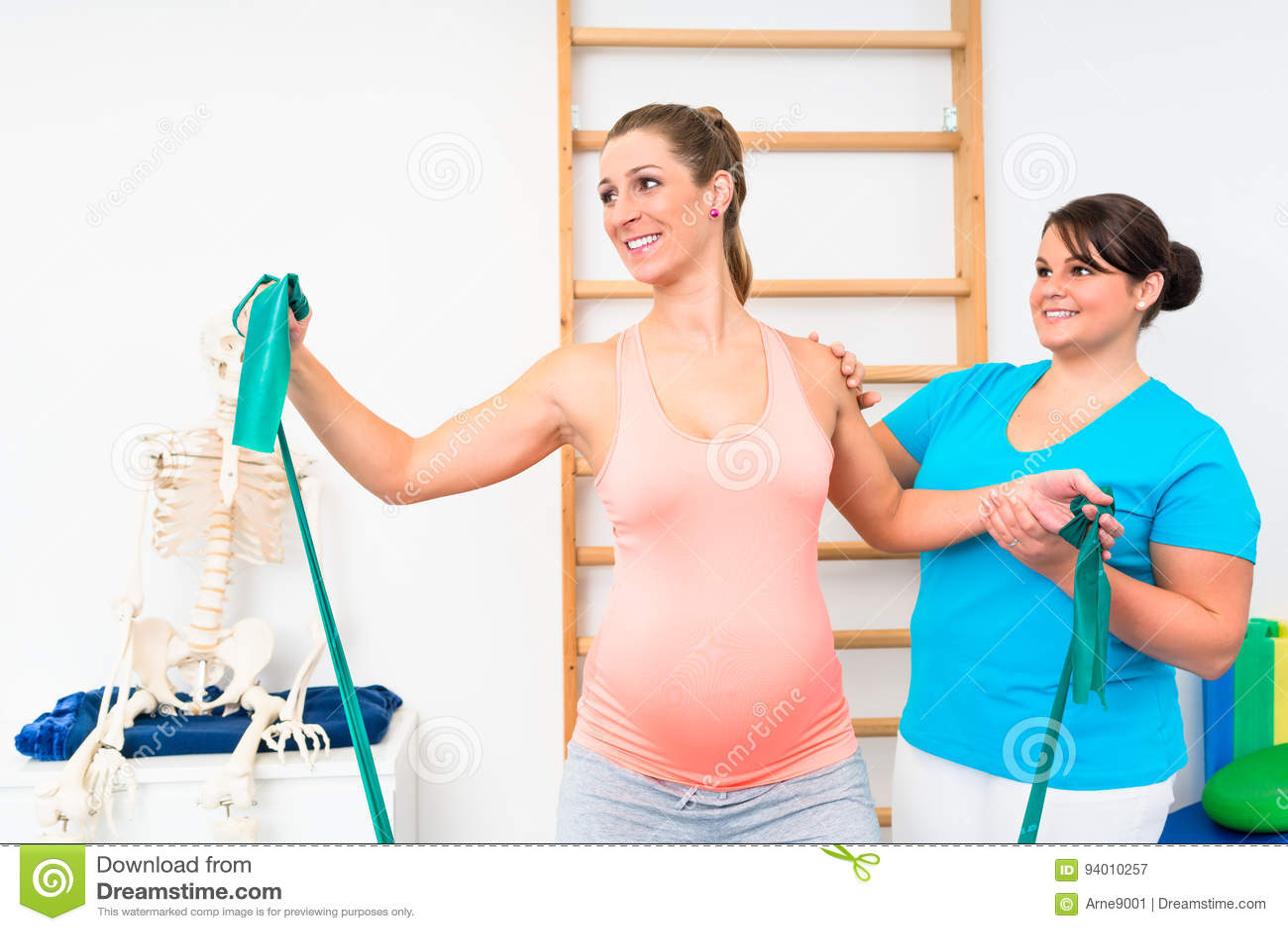 Mujer Embarazada Que Ejercita Con La Banda De La