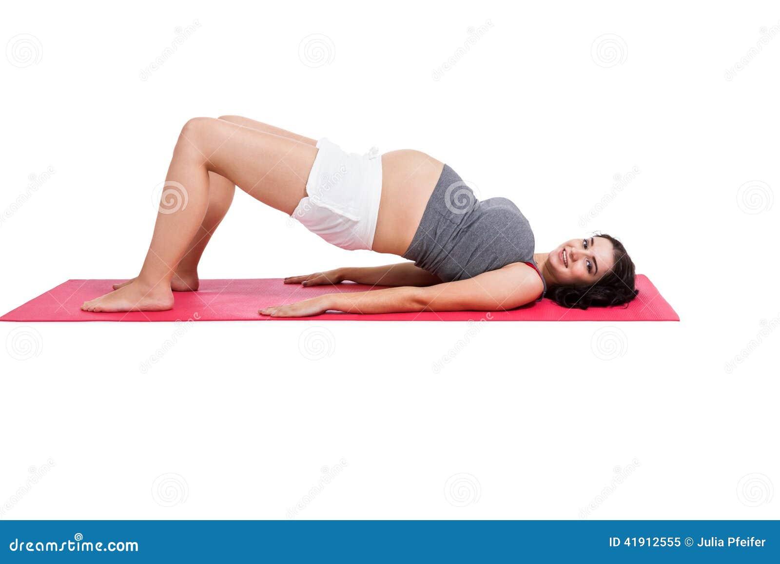 Mujer embarazada que hace ejercicios de los aeróbicos