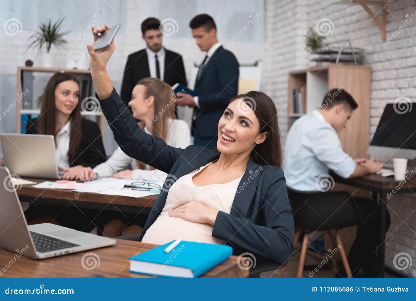 Mujer embarazada que hace el selfie en el teléfono en oficina Mujer embarazada con el equipo de trabajo