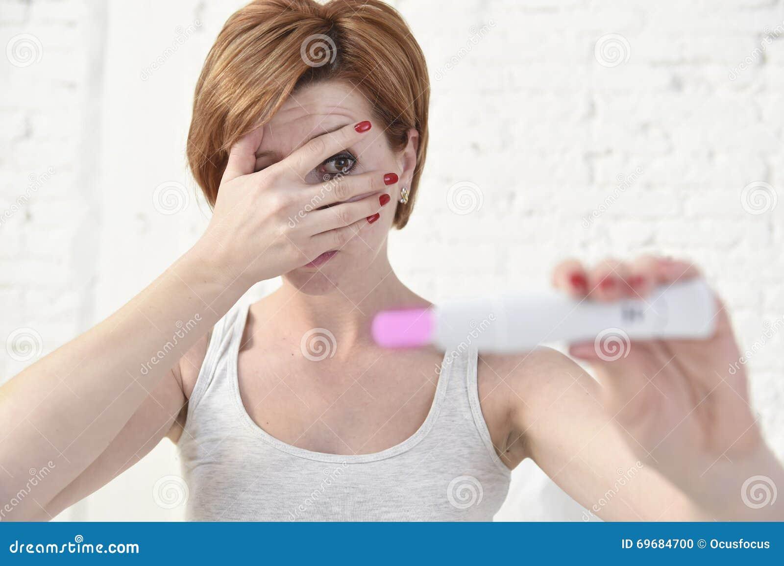 Mujer embarazada que lleva a cabo la prueba de embarazo positiva rosada que la cubre ojos con su mano