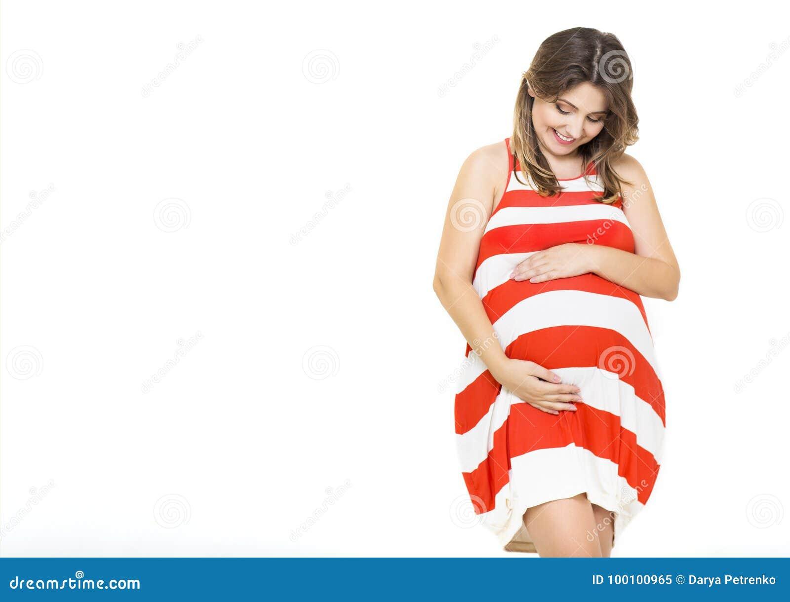 Mujer embarazada sonriente bonita joven en el fondo blanco