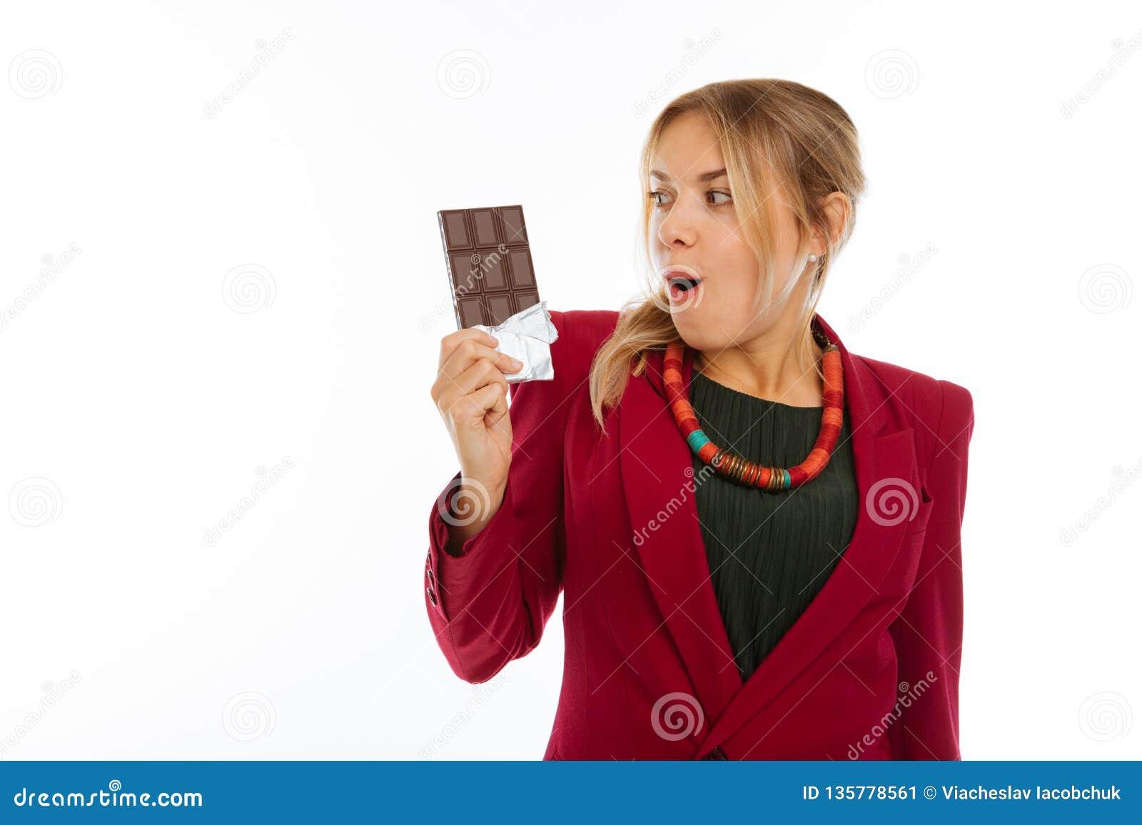 Mujer emocionada feliz agradable que mira su chocolate