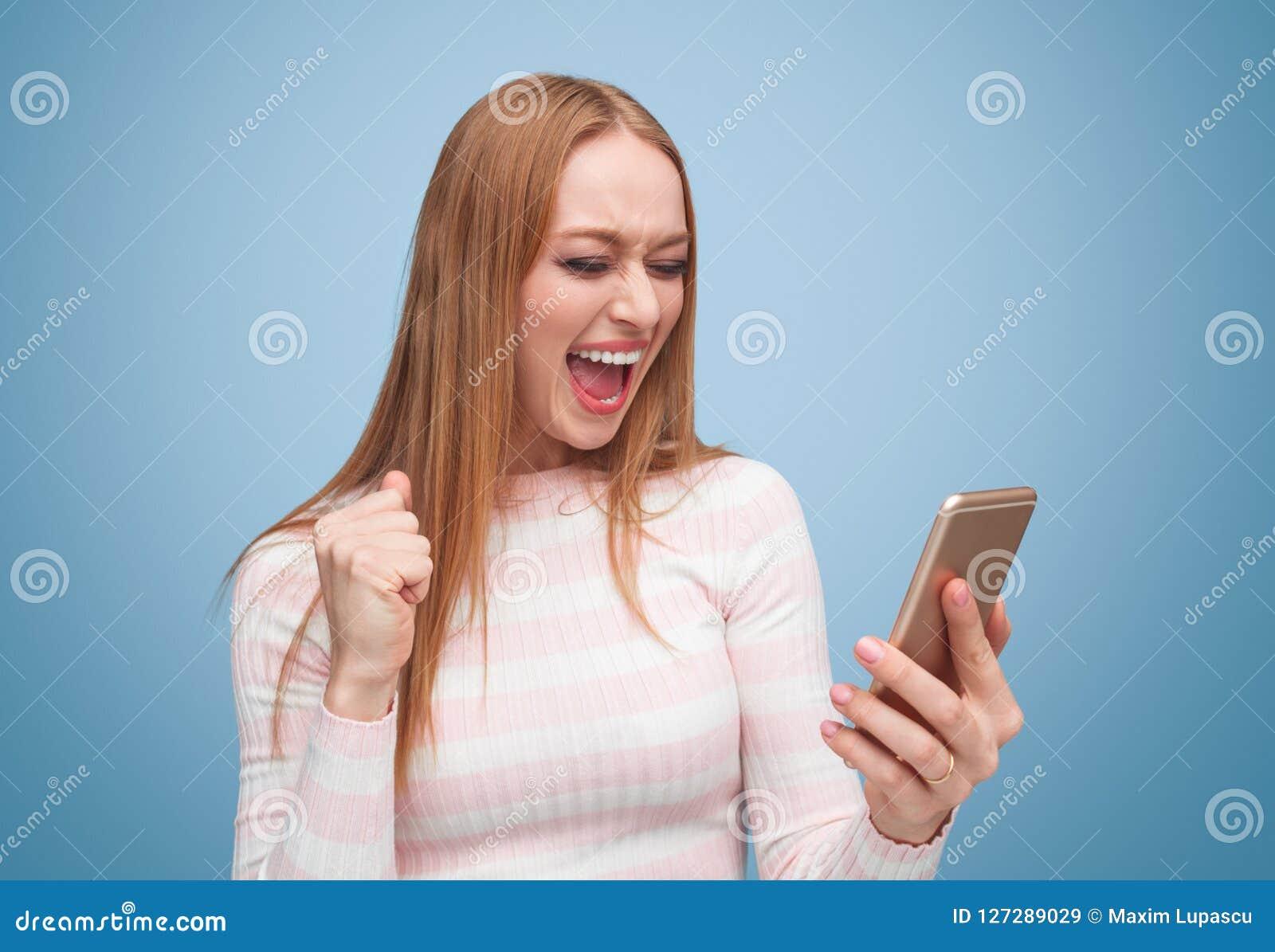Mujer emocionada que grita mientras que comprueba smartphone
