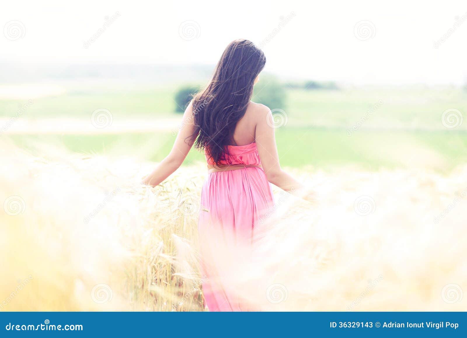 Mujer en campos del cielo del oro