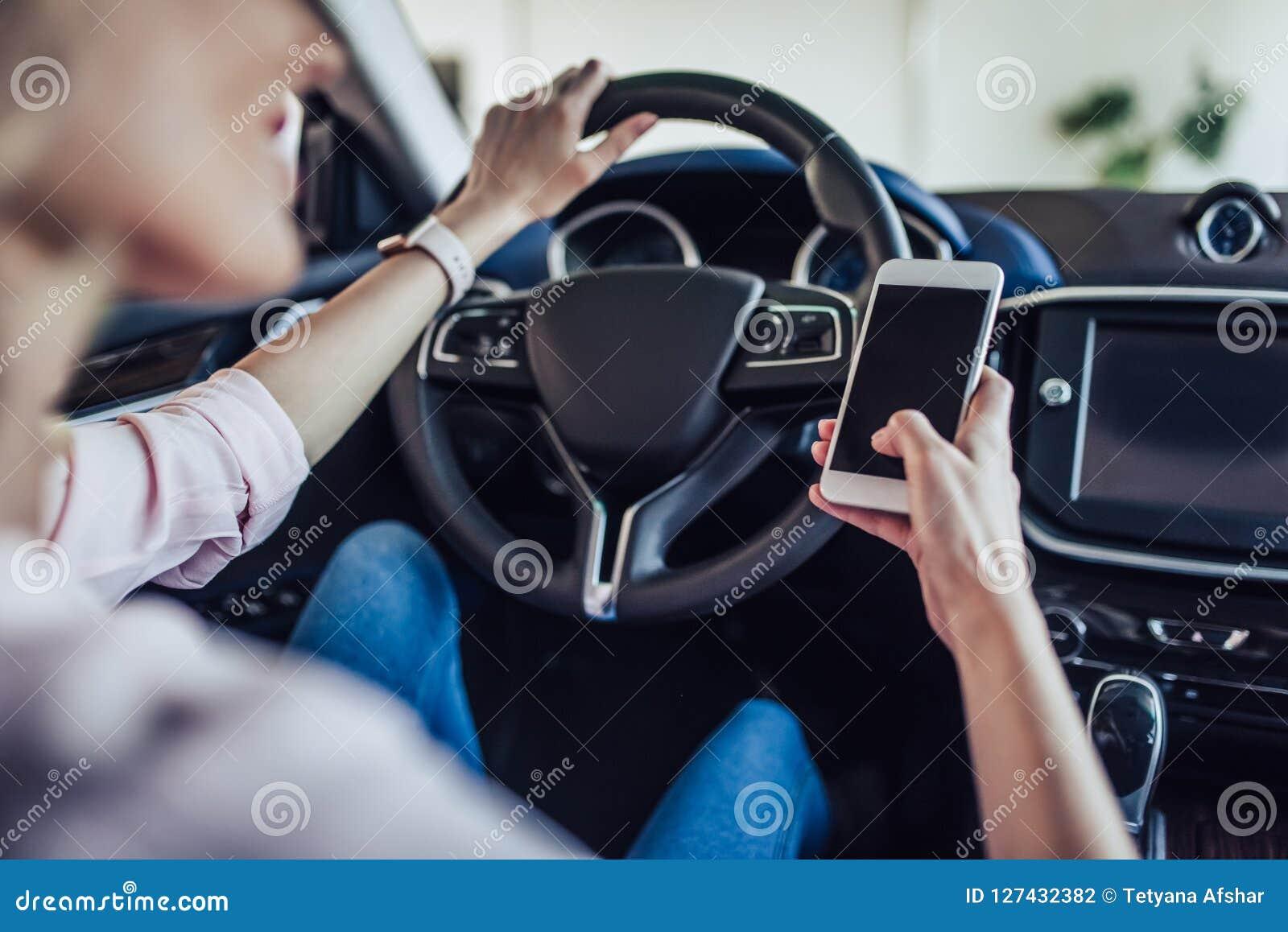 Mujer en el coche usando smartphone