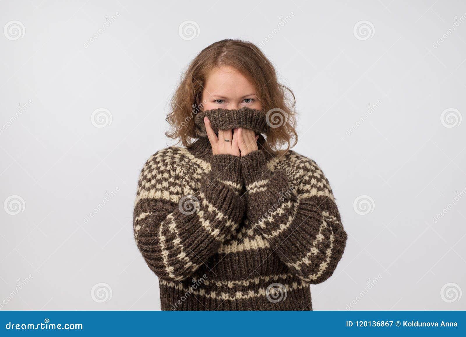Mujer en el suéter marrón caliente que oculta su cara Solamente se ven los ojos Ella quiere permanecer el anónimo