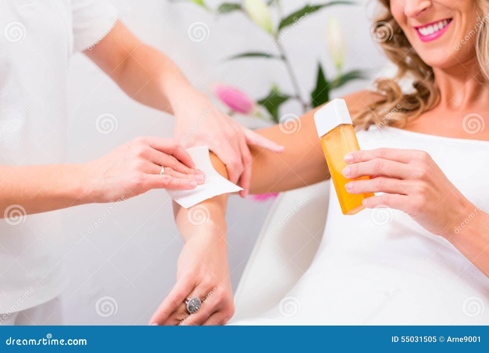 Mujer en encerar retiro del pelo en salón de belleza