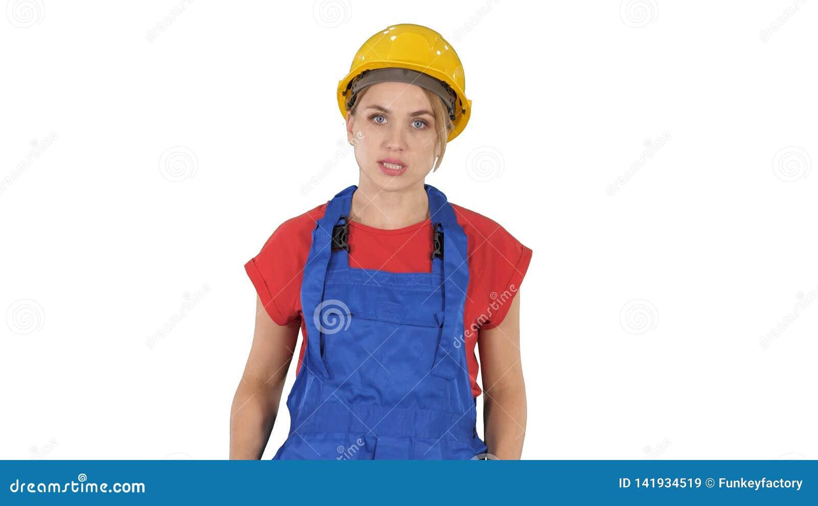 Mujer en equipo de la construcción que habla con la cámara mientras que camina en el fondo blanco