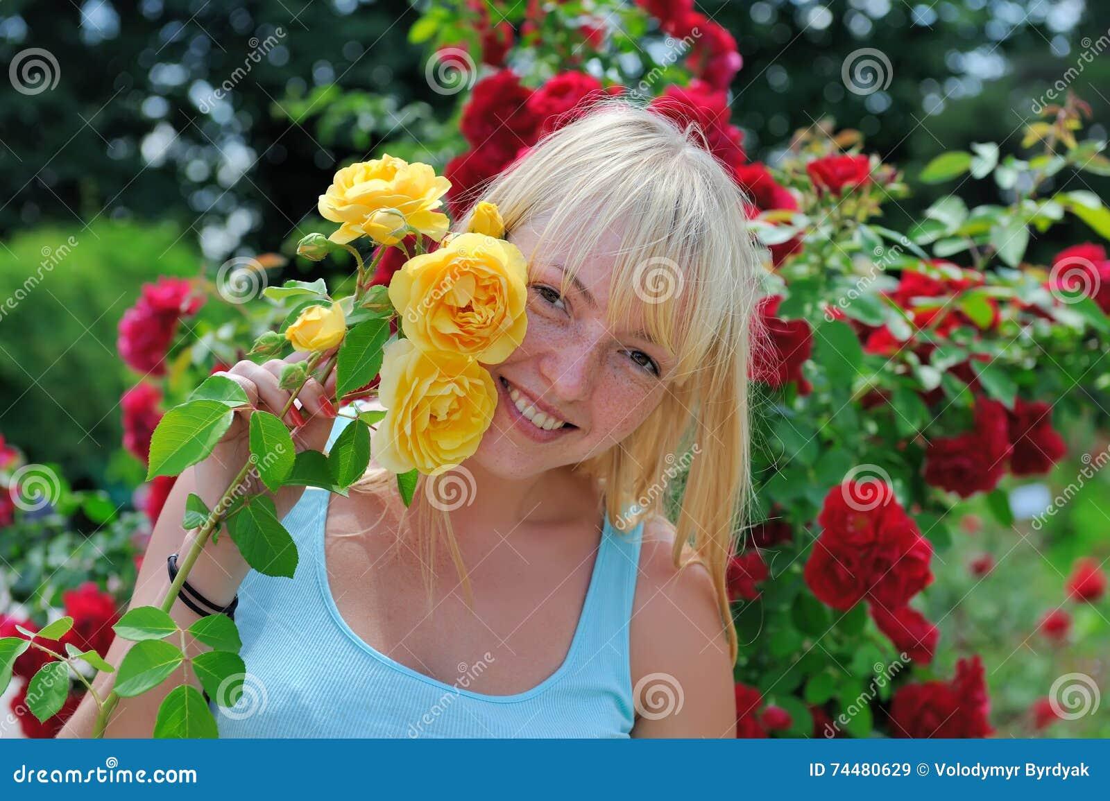 Mujer en jardín con las rosas