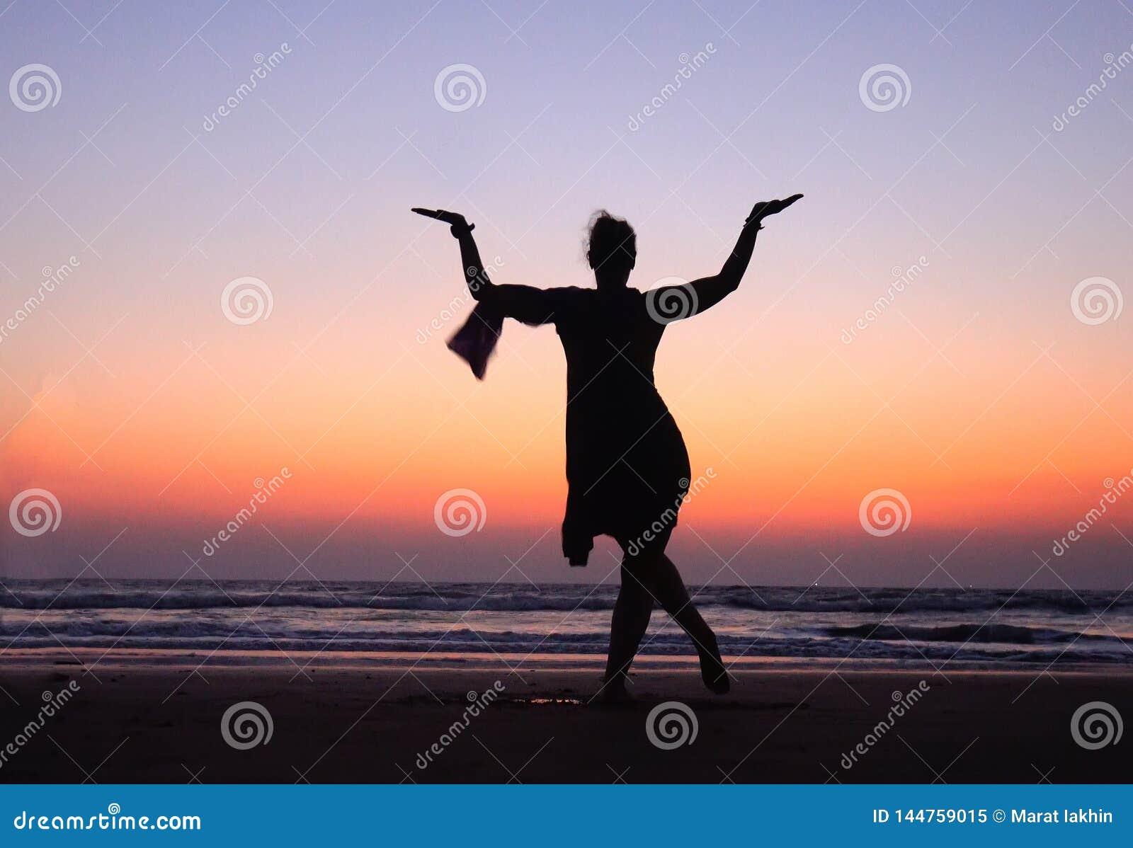 Mujer en la actitud que baila Shiva en cielo del rosa de la puesta del sol cerca del mar en la India ¡La danza es útil! Símbol