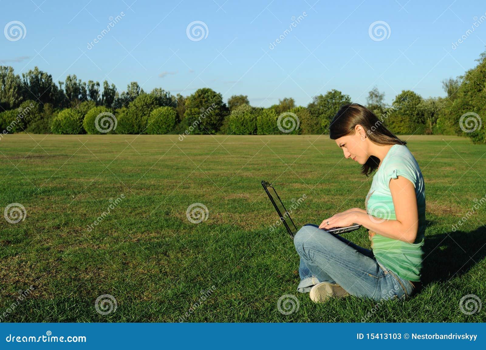 Mujer en la computadora portátil afuera