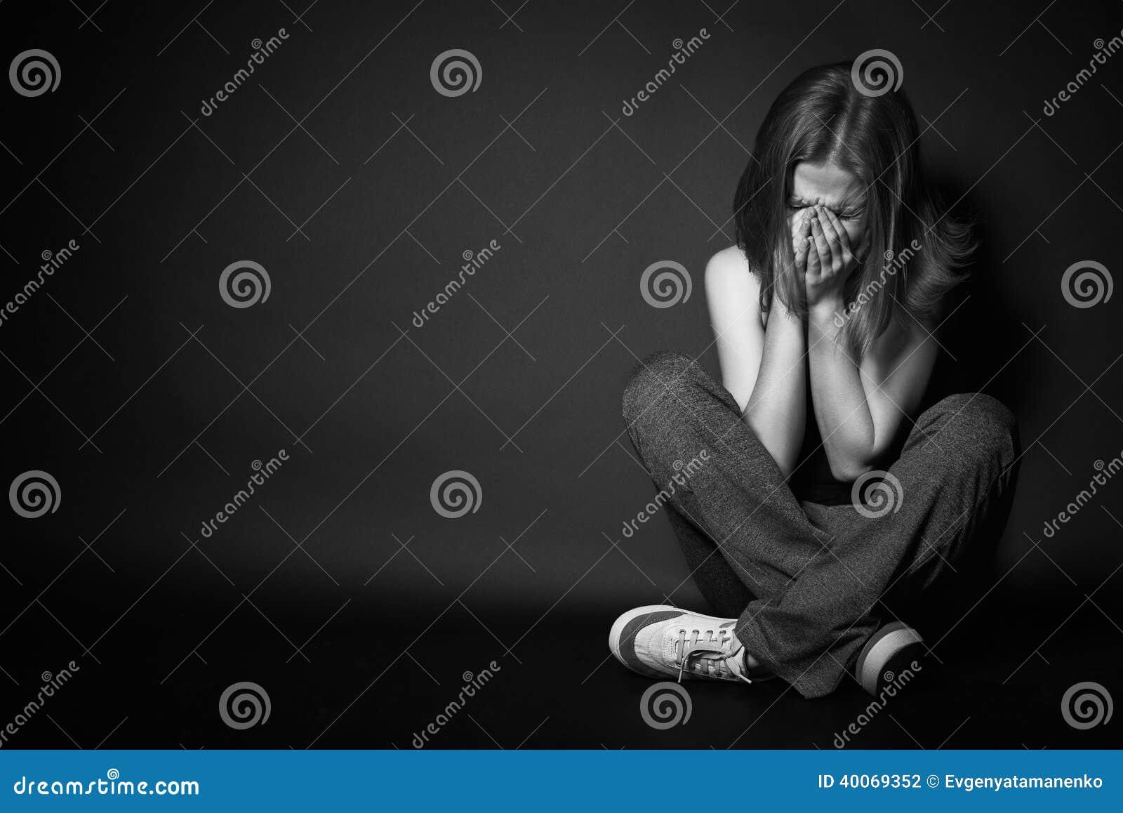 Mujer en la depresión y la desesperación que llora en oscuridad negra