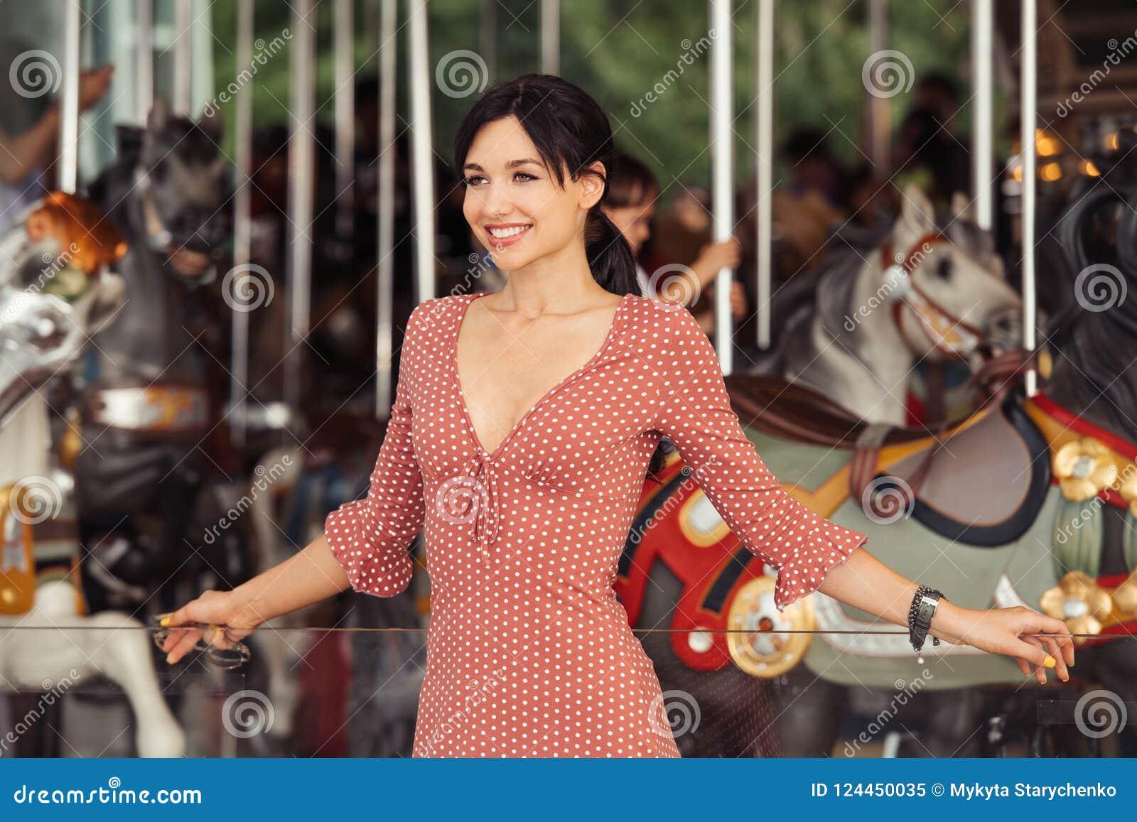 Mujer en la diversión emocionada y feliz esperando el paseo en el carrusel