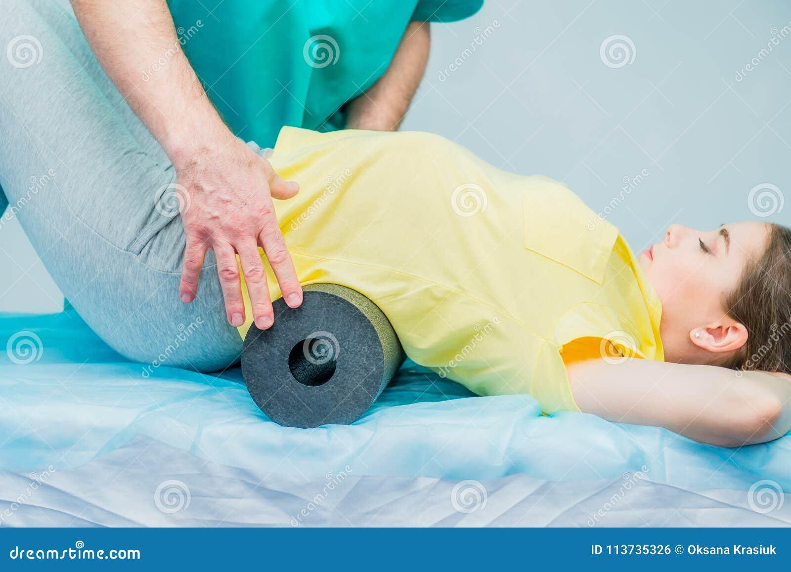 Mujer en la fisioterapia que hace ejercicios físicos con su terapeuta, ellos usando un rollo del masaje Un quiropráctico trata pa