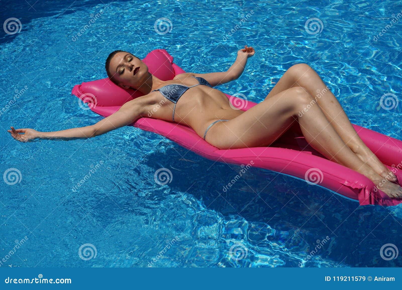 Mujer en la natación del bikini en el colchón de aire