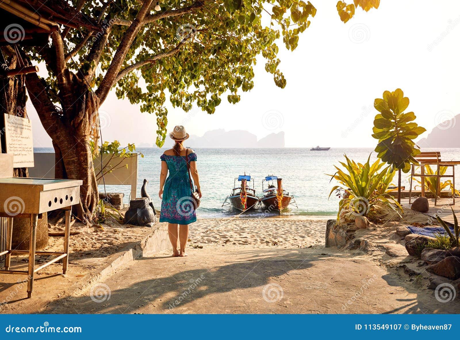 Mujer en la playa tropical de la puesta del sol