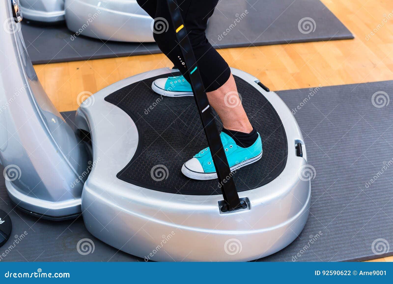 Mujer en las placas vibrantes en el entrenamiento del gimnasio